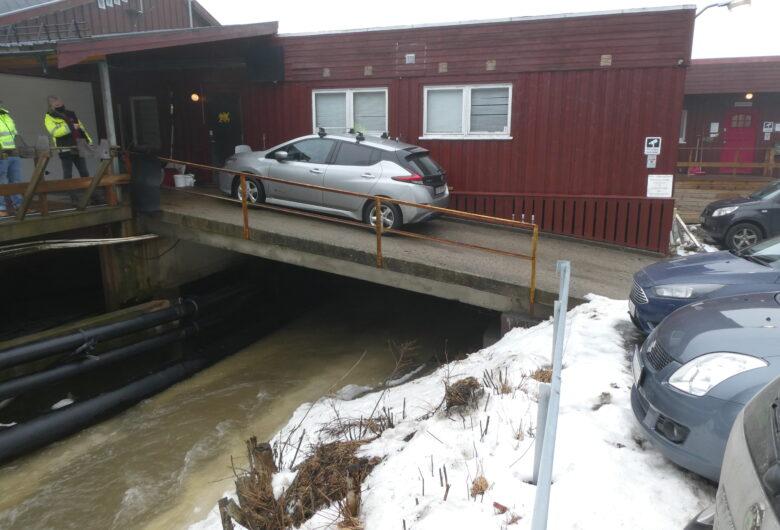 Bildet viser utsiden av forskningstasjonen. Det står en bil parkert på en bru som går opp til det røde bygget. Under renner det vann.