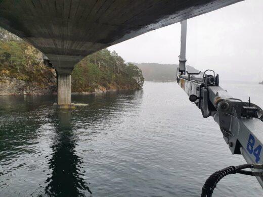 Bildet viser undersiden av en bru med vann under, og en lift.