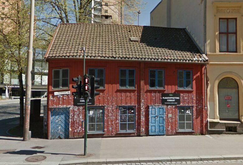 Bildet viser et slitt, rødt hus med blå dører på et gatehjørne i Oslo