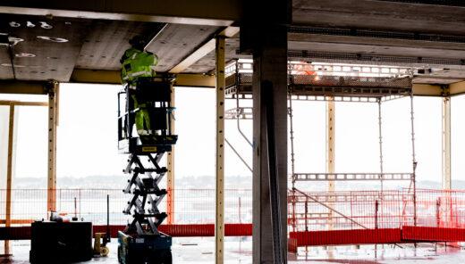 Bildet viser en heisekran med en mann som står oppunder taket. Byggeplass og betong.