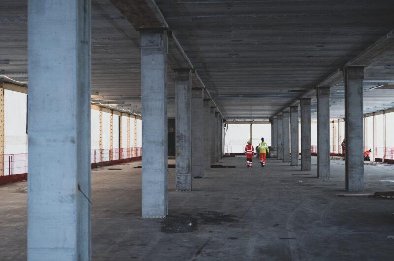 Bildet viser en tom etasje som holder på å bli bygget i betong og to mennesker