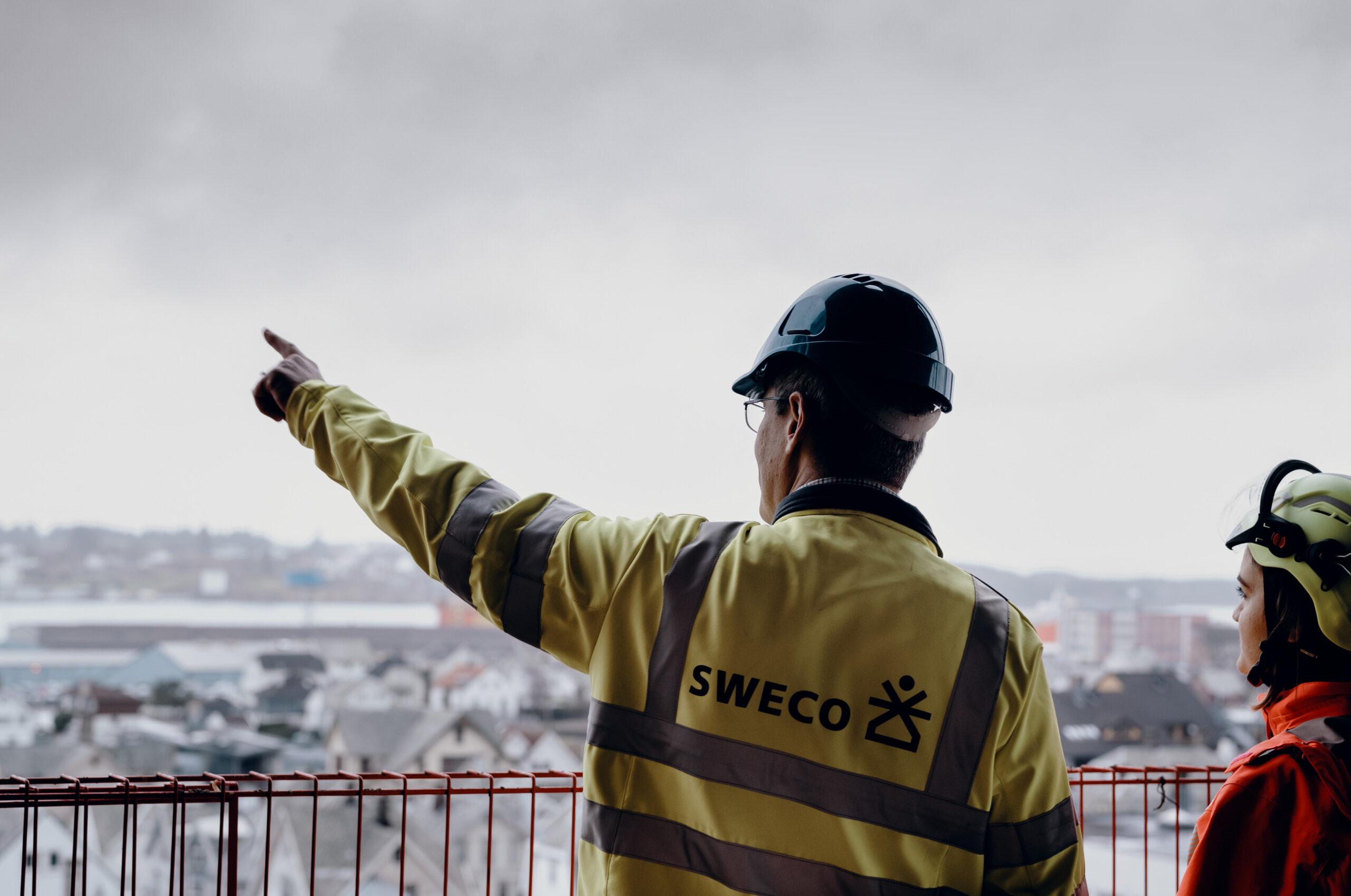 Bildet viser en mann i Sweco-jakke som peker utover Haugesund