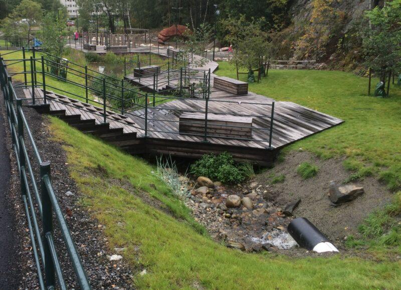 Bildet viser åpningen av Julsbergbekken et år etter åpning. Platting og sti over elven, med grøntarealer på begge sider.
