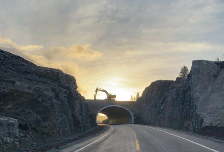 Bildet viser E6 i solnedgangen. På bildet ser man en gravamaskin som står på en bru, som vil bli kryssingsbru for rein