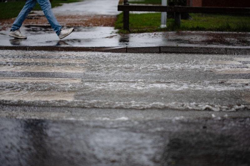 Bildet viser en person som går ved et overgangsfelt. Overgangsfeltet er oversvømt. Det er overvann som har lagt seg på asfalten.