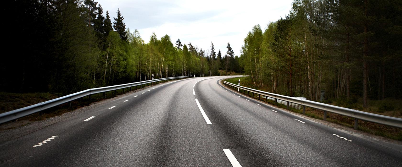 Vei i norsk natur. Våt asfalt rundt sving.