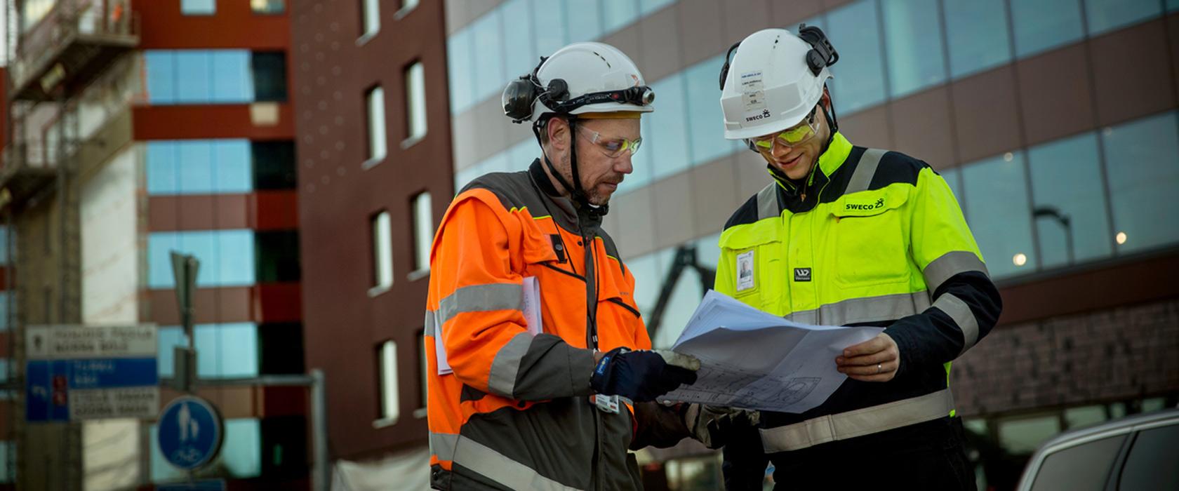 Rådgivere på byggeplass ikledd verneklær ser på tegning