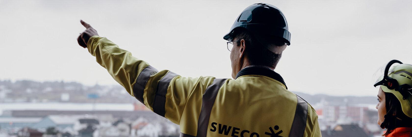Rådgiver peker utover byggeplass i grått vær. Rådgiver i hjelm og vernetøy ses bakfra og står ved siden av entreprenør.