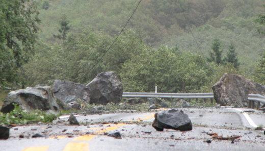 Ras fra fjellside over vei. Steinblokker sperrer veien.