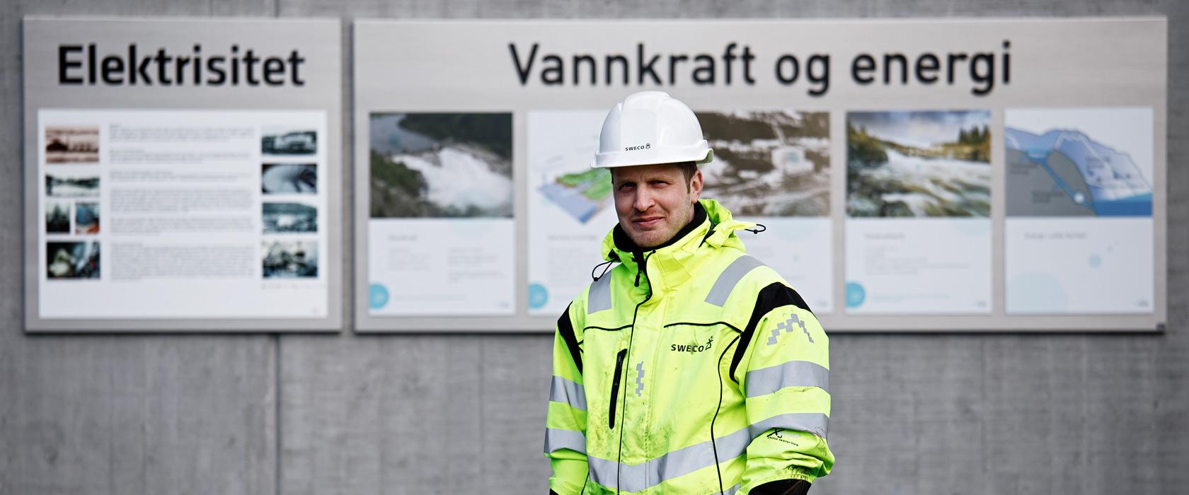 Bilde av rådgiver foran skilt hvor det står vannkraft og energi.