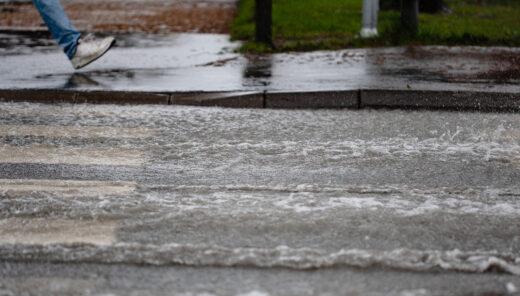 Oversvømmelse i gate, kraftig regn. Fotgjenger går på fortau, veien er oversvømt.