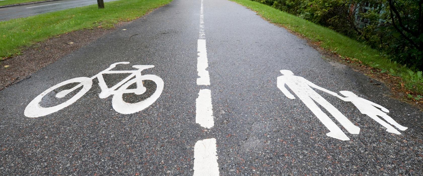 Fortau med både gang- og sykkelvei. Sykkelsymbol og menneskesymbol på asfalt.