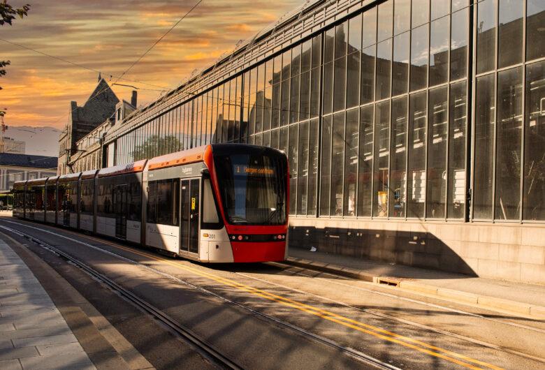 Bybanen i dagen. Bybanen kjører forbi togstasjonen i solnedgang.