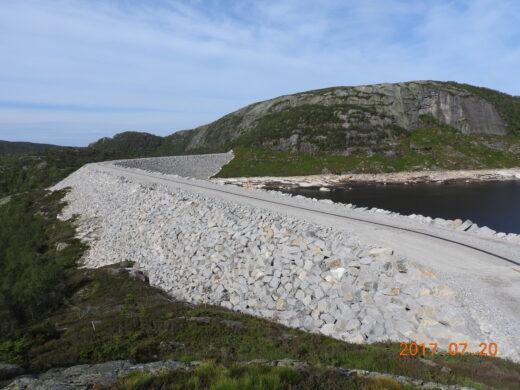 Dam Sjerkevann sett fra luften. Demningen sett fra siden, man ser både vann og natur
