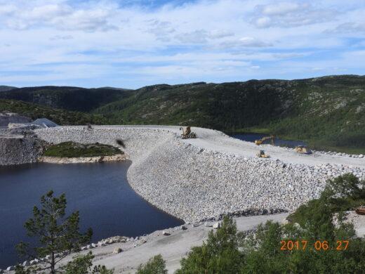 Dm sjerkevatn - det gjennomføres anleggsarbeid på dammen. Gravemaskiner står på toppen av steinmassene. Man skimter vann og natur på begge sider av dammen