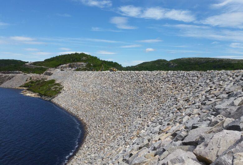 Dam sjerkevann sett fra innsiden av dammen. Her ser man vannet møte demningsveggen. Plastringen er i stein. i bakgrunnen ser man toppen av trekledde fjellsider