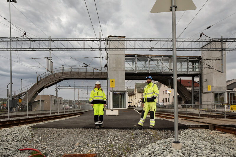 To smilende mennesker i gult verneutstyr og hjelm. Står på Moss togstasjon som er under utbygging. Overgangsbru i tre i bakgrunn.