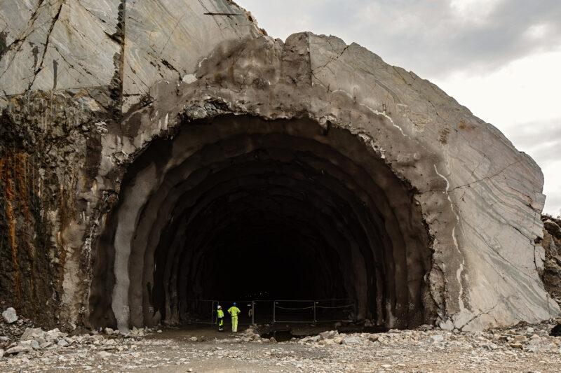 Bildet viser to anleggsarbeidere i gult verneutstyr som står foran en stor, svart tunnel.
