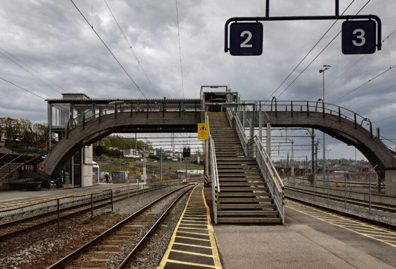 Overgangsbru over toglinjen på Moss togstasjon. Bygget i tre. Bildet viser spor to og tre. Grå himmel.