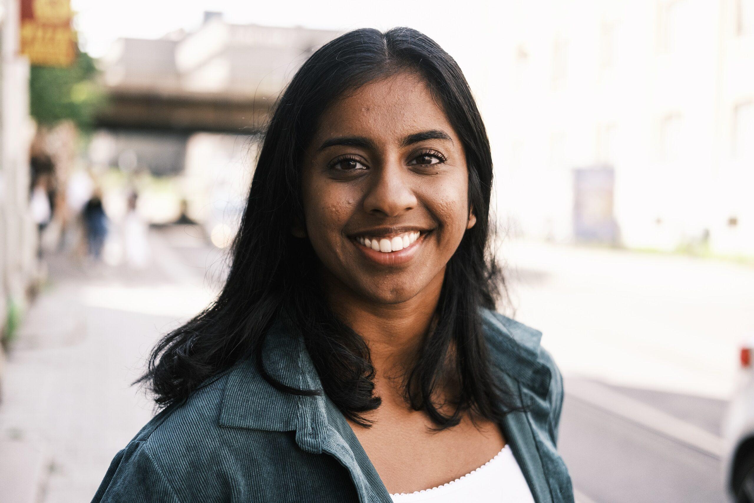 Nærbilde av en jente som står på gaten og smiler til kamera