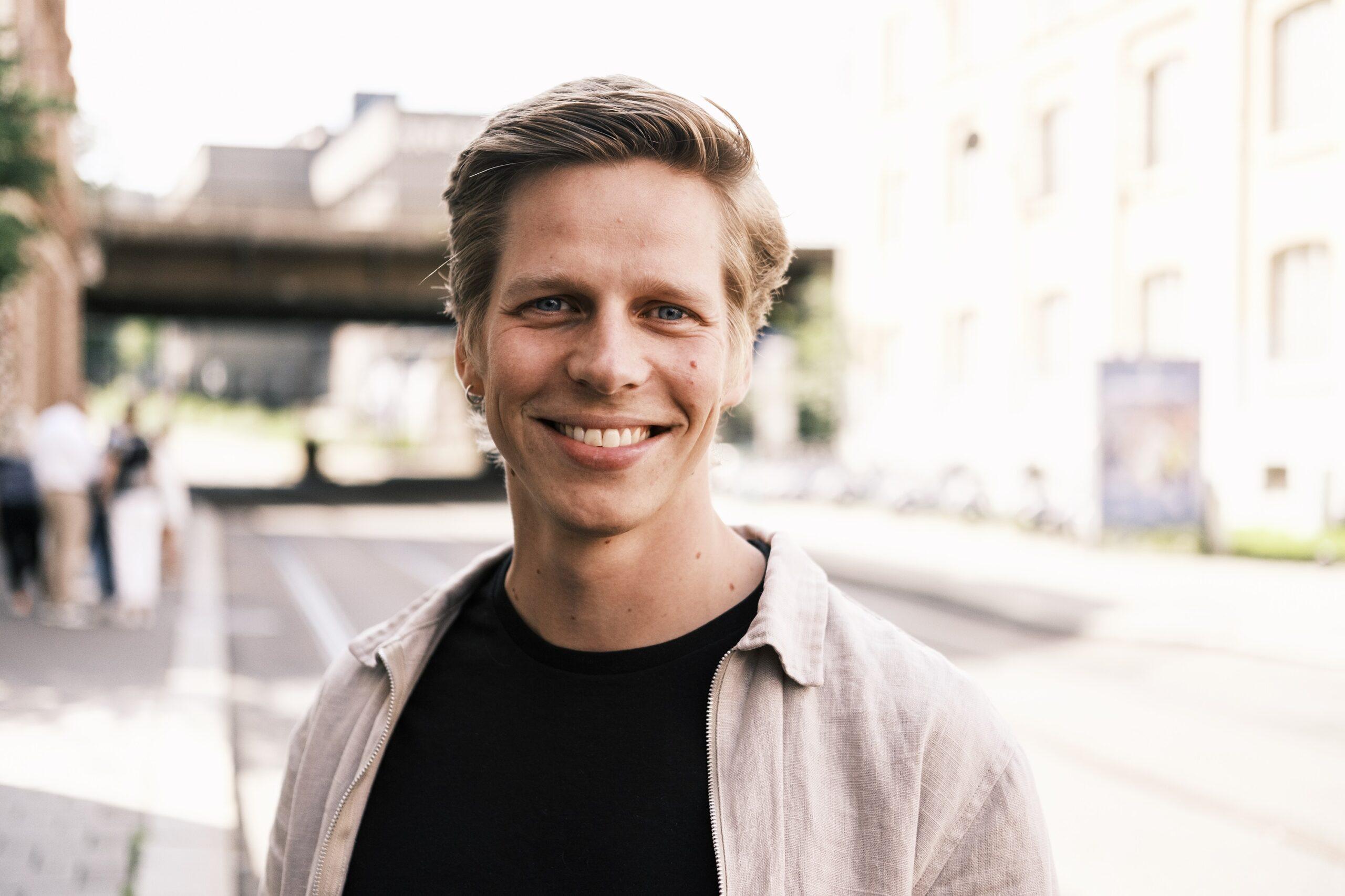 Nærbilde av en gutt som står på gaten og smiler til kamera