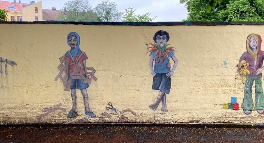 En gul vegg er malt med ulike bilder av barn.