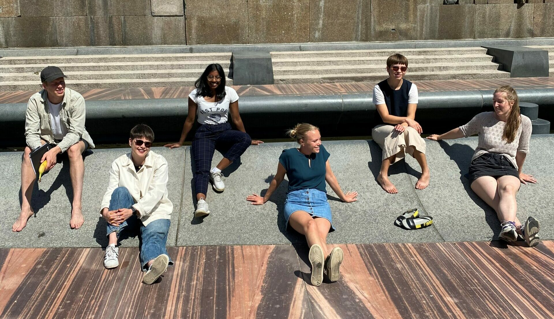 En gutt og fem jenter sitter i en park bestående av asfalt og en bekk i bakgrunn