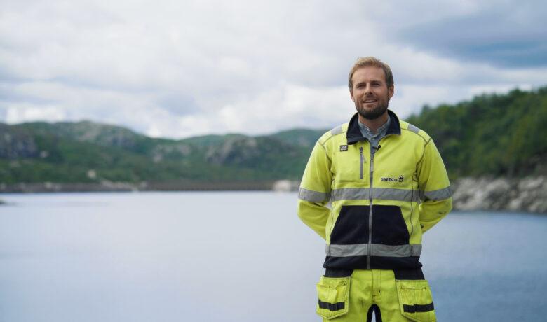 Mann i gule arbeidsklær står foran dam Skjerkadammen.