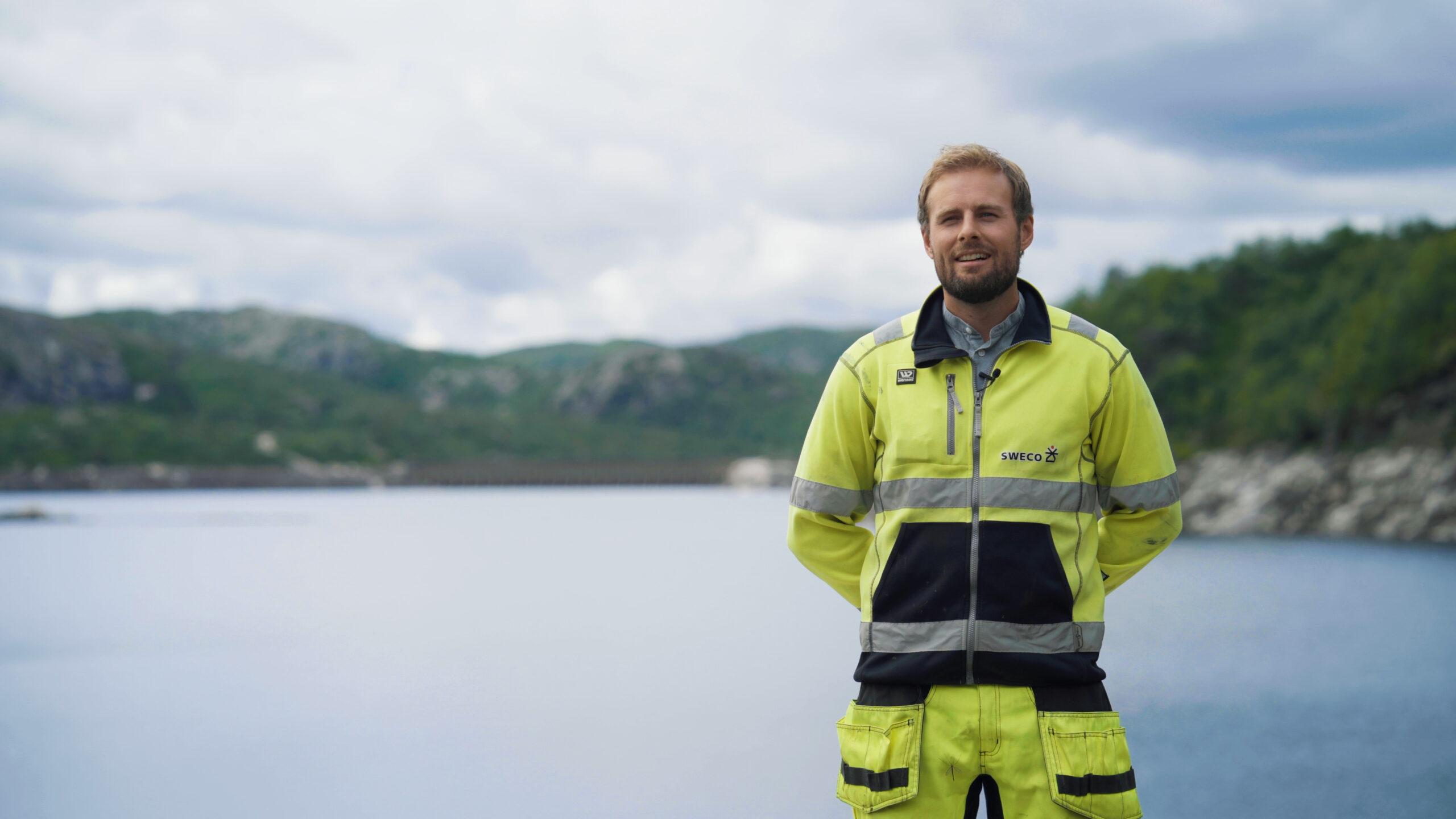 Mann i gule arbeidsklær står foran dam Skjerka