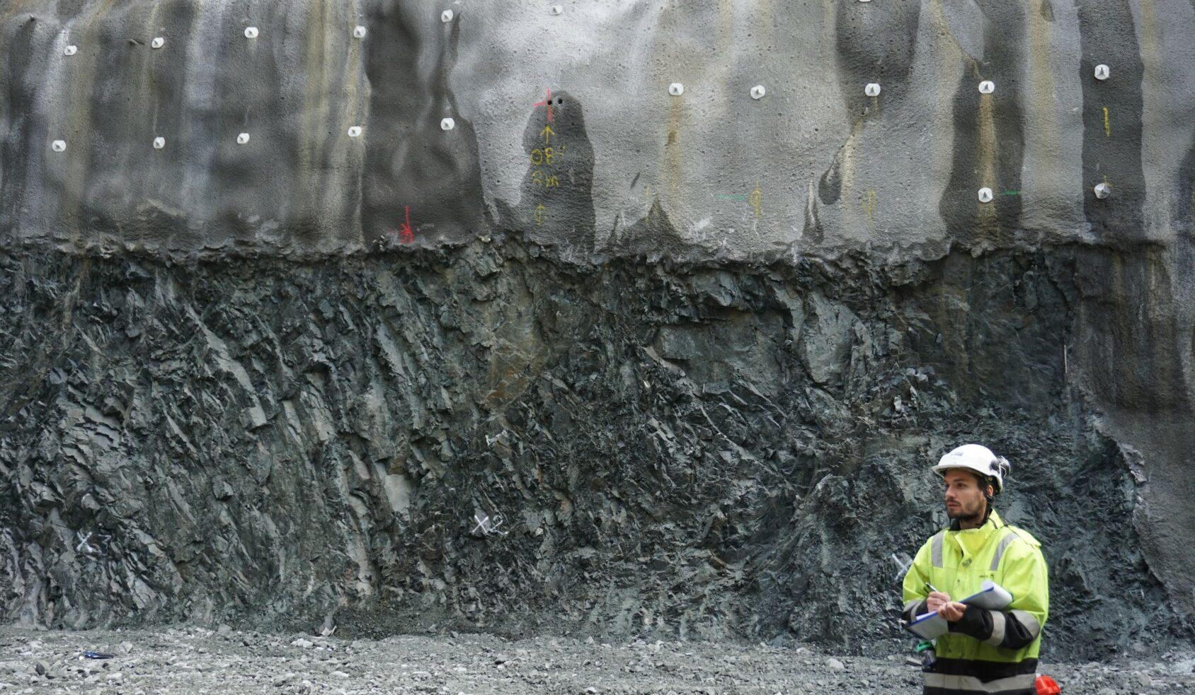 En mann i gule arbeidsklær og hjelm på byggeplass
