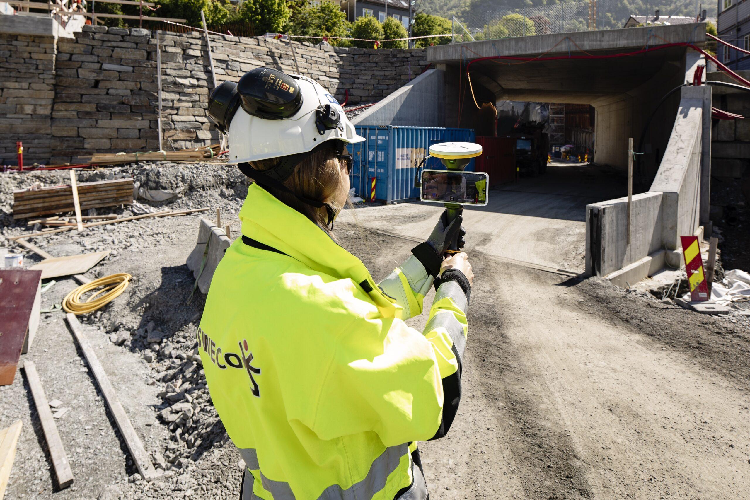 Astrid greve rokne, gjennomfører digital befaring via iphone på byggeplass