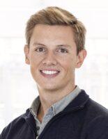 Mann med blondt hår, skjorte og genser smiler til kamera