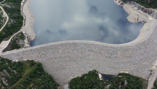 Oversiktsbilde over en nybygget dam. Grå steiner dekker den store dammen, blått hav og grønn skog rundt.