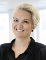 Portrett av en kvinne med blondt, kort hår, som smiler inn i kameraet