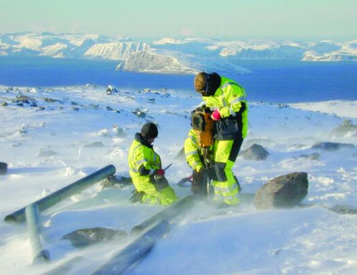 Tre ingeniører i vinterlandskap borer vindmølle